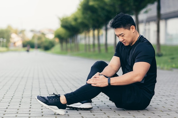 Asian man after fitness workout and jogging sits on the ground and suffers from leg pain, massages leg muscles