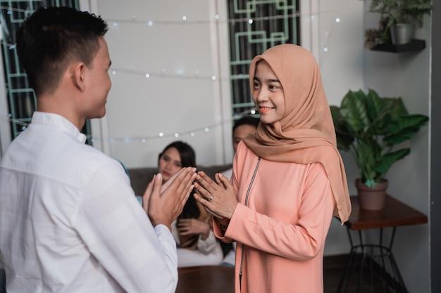 Азиатский мужчина и женщина в хиджабе приветствуют друг друга