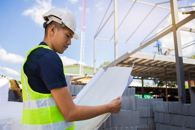 白い安全ヘルメットをかぶったアジアの男性と女性の土木技師の紙の計画の建物の建築家は、建設現場を見てください。