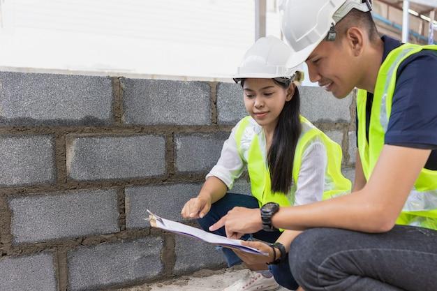 건설 현장에서 흰색 안전 헬멧 봐 아시아 남자와 여자 토목 기사 종이 계획 건물 건축가.