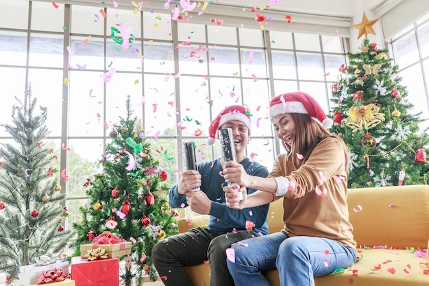 거실에서 크리스마스를 축하하는 아시아 남자와 여자. 아시아 행복한 커플은 집에서 소파에 앉아 있는 산타 모자에 크리스마스 트리가 있는 종이 불꽃놀이와 선물 상자를 당깁니다.