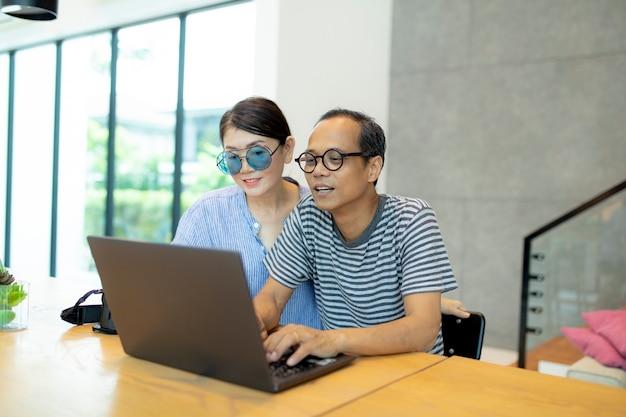 アジアの男性と女性が自宅のリビングルームでコンピューターのラップトップに取り組んで