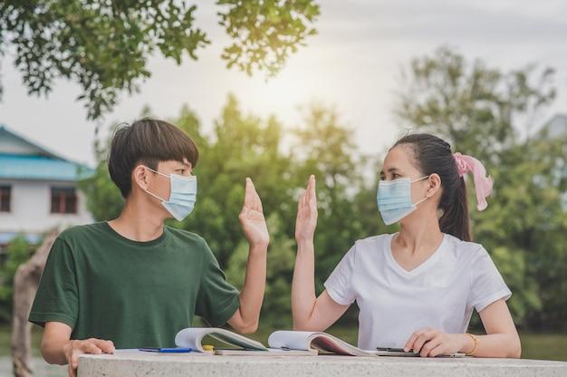 Азиатские мужчины и женщины возвращаются в школу в маске для лица и пожимают друг другу руки, сохраняя новую норму, не трогая социальное дистанцирование