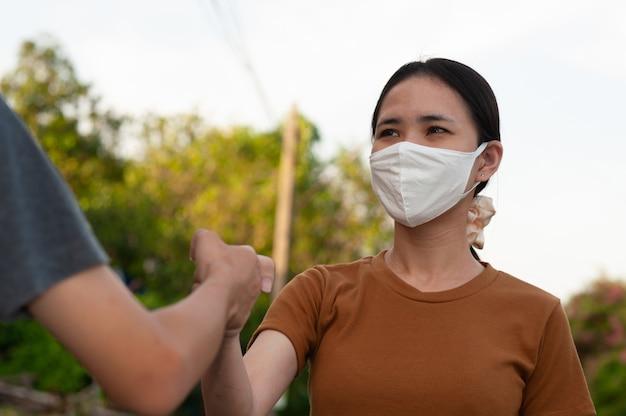 Азиатские мужчины и женщины пожимают руку, не касаясь, чтобы защитить концепцию вируса короны новое нормальное социальное дистанцирование