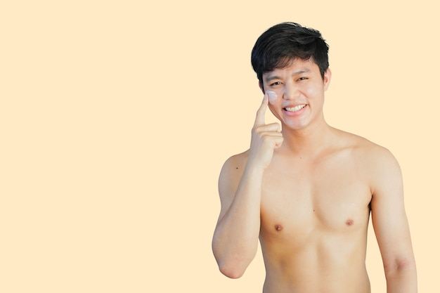 Asian man applying sunscreen uvprotection on face and smile isolate on cream backgrounf