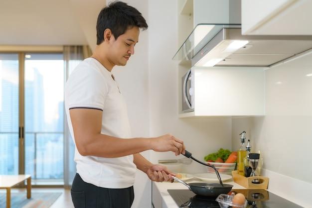アジア人男性が自宅のキッチンで目玉焼きをフライパンで揚げてアメリカンブレックファーストを作っています。