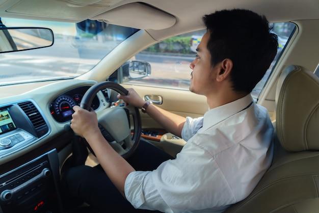 アジア人男性が朝仕事に行くために街の通りを運転しています