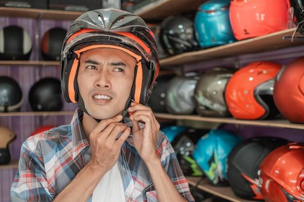 アジア人男性がヘルメットをヘルメットのディスプレイラックに装着しながらストラップバックルを取り付ける