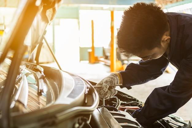 ガレージで作業車にレンチとドライバーを使用してアジア人自動車整備士。
