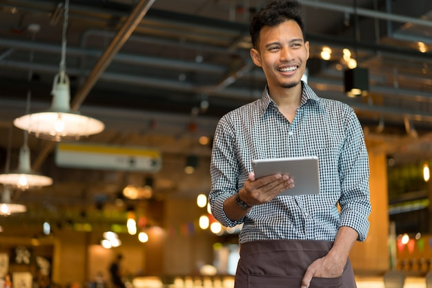 Asian man barista holding tablet and looking forward at inside restaurant cafe shop