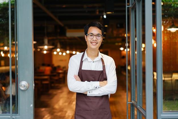 アジア人の男のバリスはコーヒーカフェの店に立つ