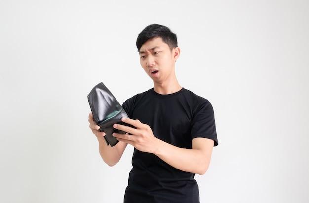 아시아 남자 검은 셔츠는 손에 지갑을 보고 흰색 격리된 가난한 남자 개념에 충격을 느낀다