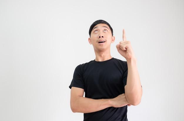 Азиатский мужчина в черной рубашке указывает пальцем и смотрит на копию пространства