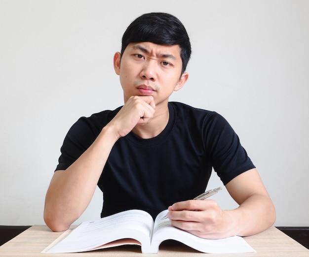 아시아 남자 검은 셔츠 심각한 얼굴과 책상에 책으로 턱을 만지고 카메라를 봐