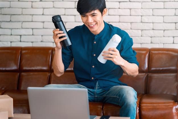Азиатский мужчина-блогер показывает бутылку перед камерой, записывая видео влог в прямом эфире