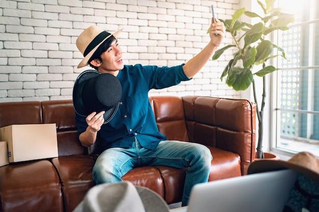 Азиатский мужчина-блогер показывает шляпу перед камерой, записывая видео влог в прямом эфире