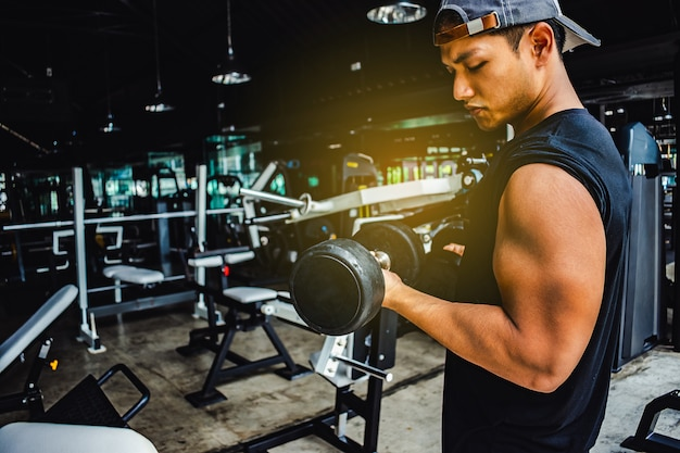 Asian man bodybuilder with dumbbell weights power handsome athletic exercises.