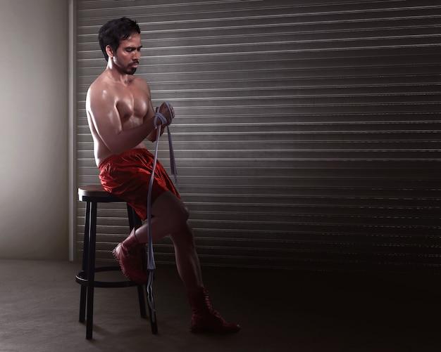 Asian man boxer sitting while wearing white strap