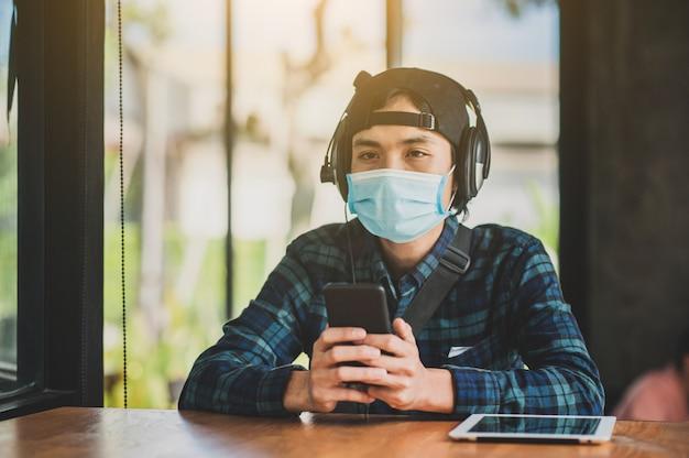Азиатский человек бизнес использовать маску, сидя в кафе образ жизни новое нормальное социальное дистанцирование после блокировки вируса короны