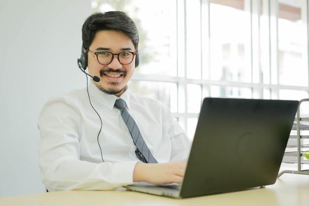 アジア人男性コールセンターエージェントはヘッドセットデバイスを着用し、テレマーケティングとヘルプデスクの概念のために働いて笑顔