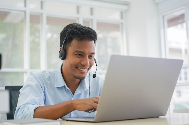 Asian man call center agent wear headset device  working in operation room