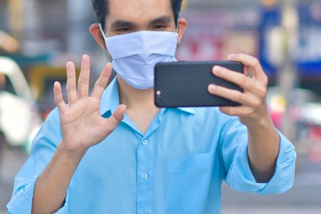 アジアの男性が市の通りに医療マスクで電話をかける