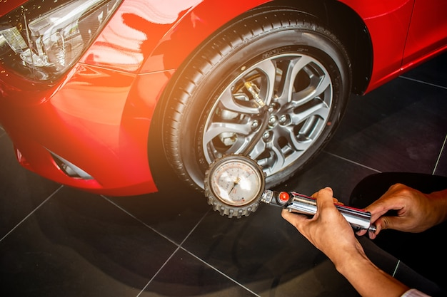 Asian man car inspection measure quantity inflated rubber tires