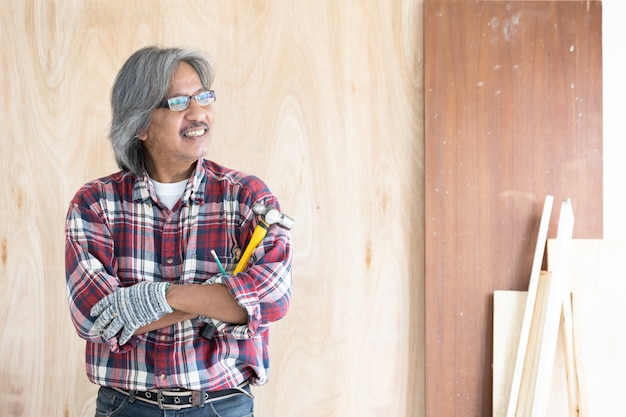 Asian man carpenter working on woodworking table in home carpentry shop