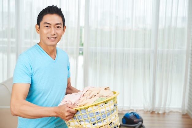 Asian man carrying full laundry basket at home