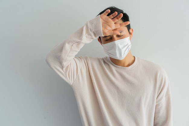 Asian man checking body's temperature on forehead for coronavirus prevention concept