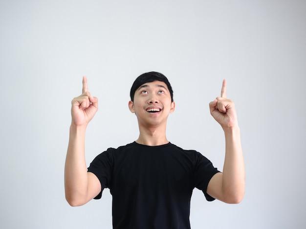 Азиатский мужчина веселый указывает двойной палец и смотрит вверх на белом фоне