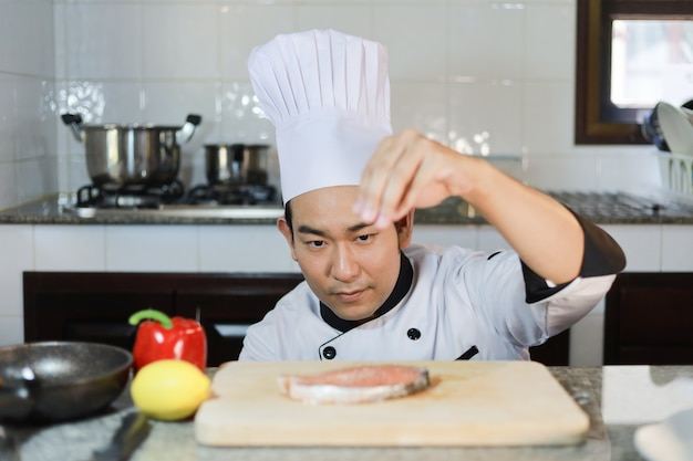 Asian man chef cooking food  in restuarant