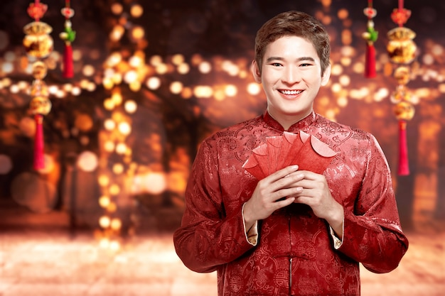 Asian man in a cheongsam costume holding red envelopes