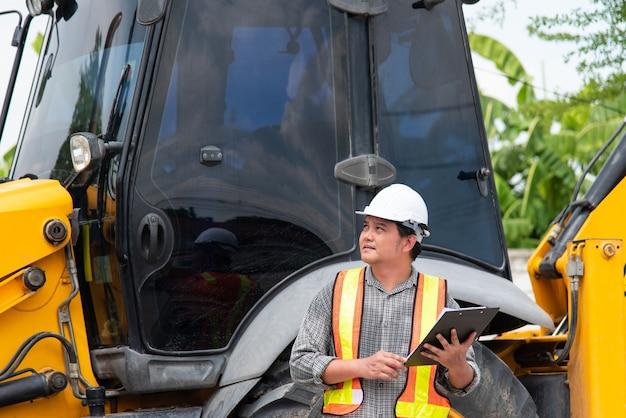 アジア人男性の土木建設エンジニアの労働者または建築家で、ヘルメットと安全ベストを使用して、建物や建設現場で青写真や計画を確認するための紙のボードノートを保持しています