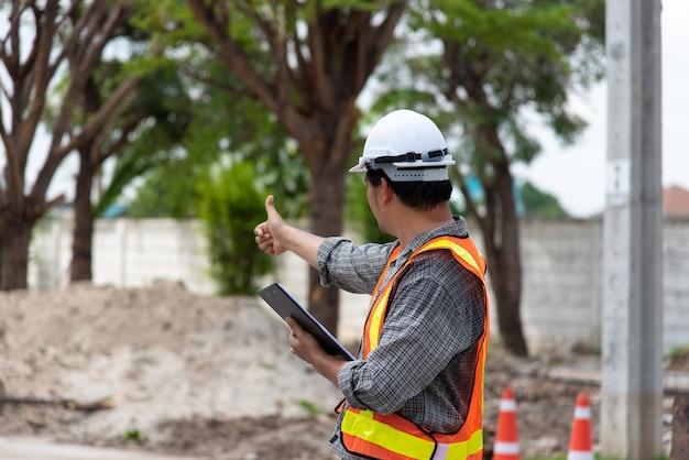 Азиатский мужчина, инженер-строитель или архитектор в шлеме и защитном жилете, работает и держит бесконтактный планшет