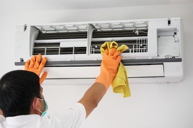 극세사 천으로 에어컨을 청소하는 아시아 남자