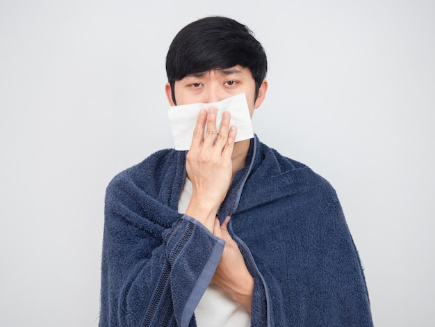 아시아 남자는 코에 조직을 닫고 아프다고 느끼며 수건 초상화로 몸을 가린다