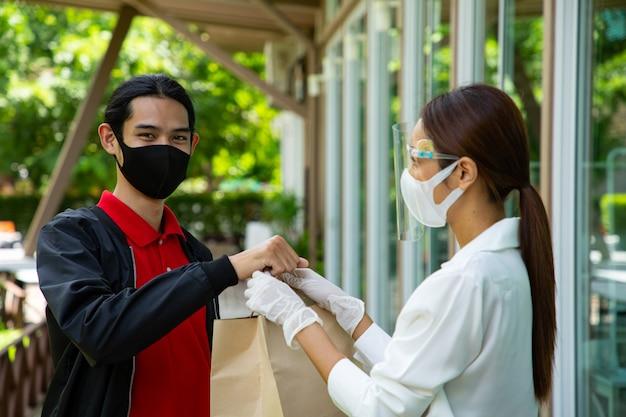 아시아 남자가 음식을 가져가러 옵니다. 배달원이 레스토랑에서 빵을 가져옵니다. 웨이트리스가 고객에게 음식을 가져다줍니다. 마스크를 쓴 새로운 일반 고객이 음식을 가져갑니다.
