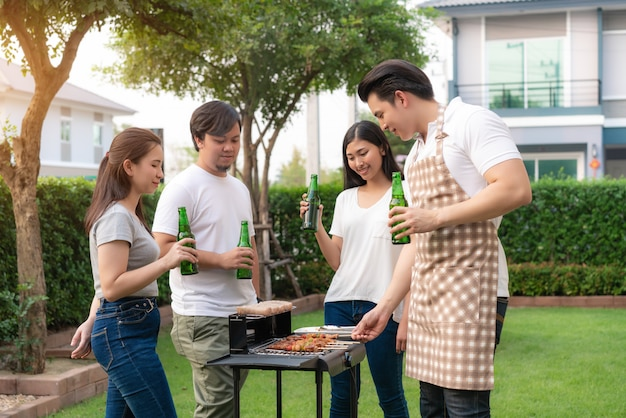 Asian man cooking barbecue grill and sausage for a group of friends to eat party in garden at home.