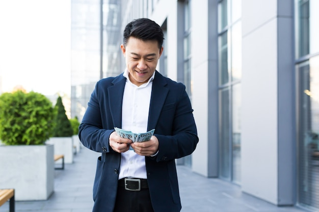 Asian man counts money near the office, happy businessman got a lot of cash
