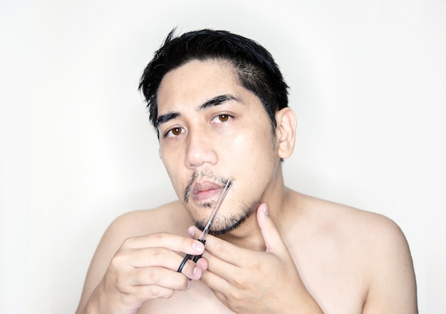 Asian man cutting moustache to decor hair fashion