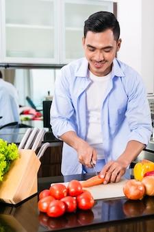 Азиатский мужчина режет овощи на домашней кухне, готовит салат