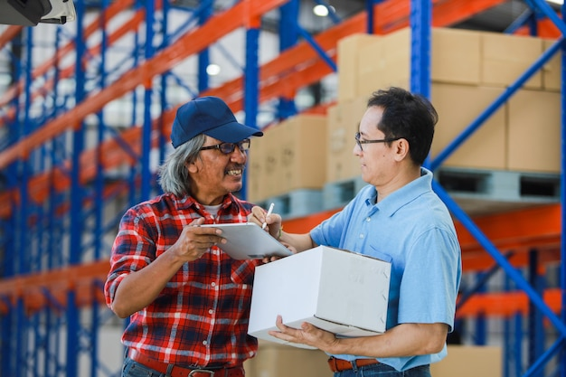 Asian man delivery good box to customer in factory and signature on tablet smile and good service , logistic shopping online concept