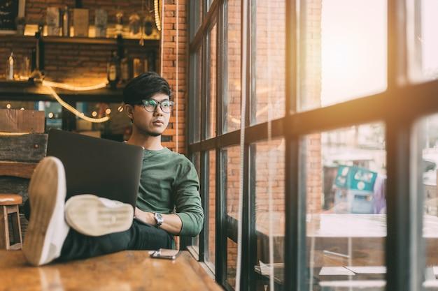 Азиатский мужчина делает внештатную работу, сидя на портативном компьютере.