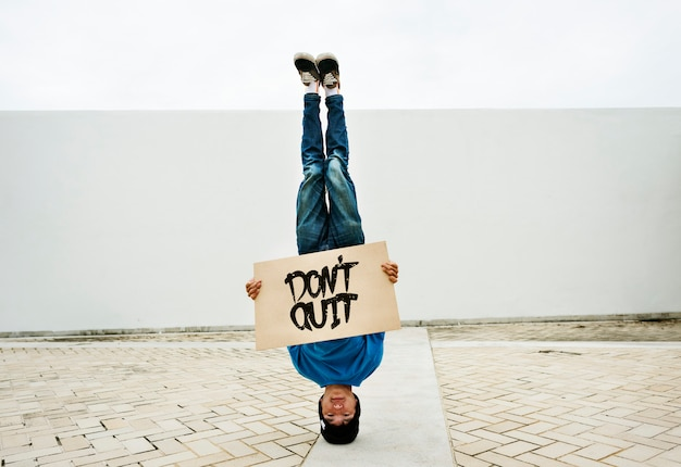 Asian man doing a headstand holding a don't quit banner