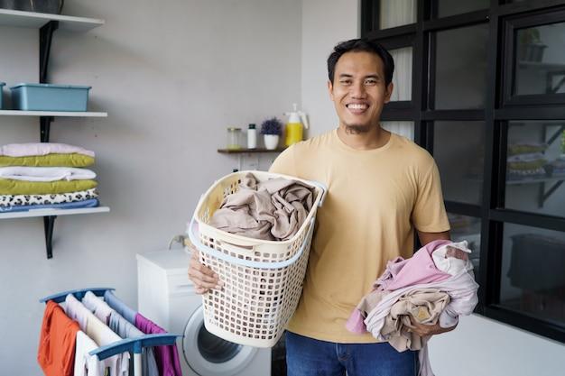 집에서 세탁을 하 고 아시아 남자 세탁기에 옷을로드