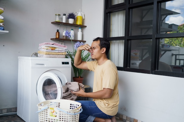Asian man doing laundry at home loading clothes into washing machine bad odor