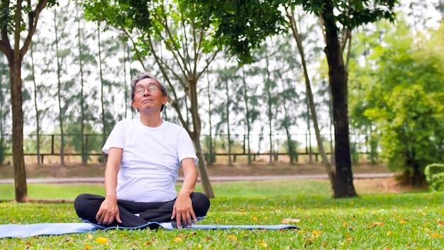 Азиатский человек, занимаясь йогой в парке.
