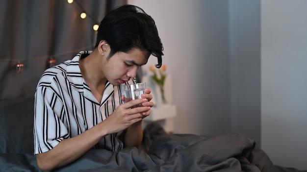 夜、ベッドに座ってグラスから水を飲むアジア人男性。