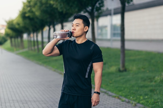 Asian man drinks water after fitness workout and jogging tired